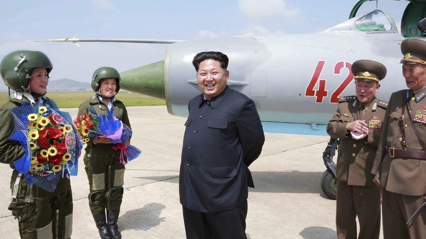 June 22, 2016: North Korean leader Kim Jong Un smiles as he attends a flight training session by female fighter pilots Jo Kum Hyang and Rim Sol in this undated photo released by North Korea's Korean Central News Agency.