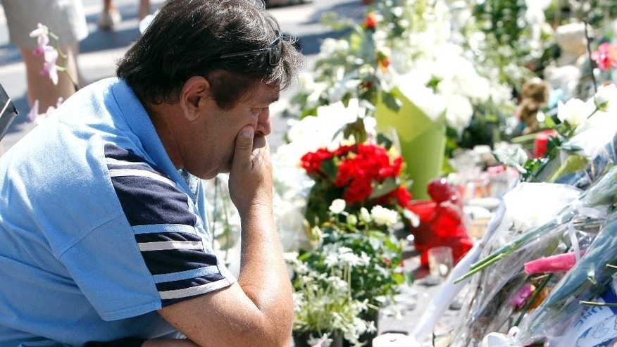 A man reacts as he looks flowers placed at a new memorial in a gazebo in a seaside park of the Promenade des Anglais in Nice, southern France, Tuesday, July 19, 2016. Joggers, cyclists and sun-seekers are back on Nice's famed Riviera coast, a further sign of normal life returning on the Promenade des Anglais where dozens were killed in last week's Bastille Day truck attack. (AP Photo/Claude Paris)