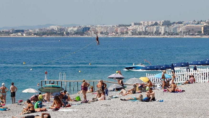 People sunbath in the beach of the Promenade des Anglais in Nice, southern France, Tuesday, July 19, 2016. Joggers, cyclists and sun-seekers are back on Nice's famed Riviera coast, a further sign of normal life returning on the Promenade des Anglais where dozens were killed in last week's Bastille Day truck attack. (AP Photo/Claude Paris)