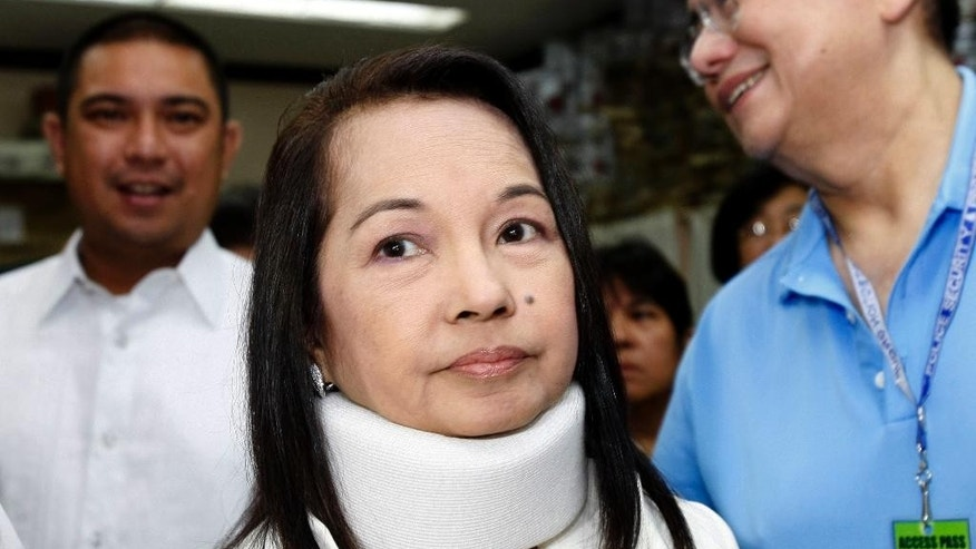 FILE - In this Feb. 23, 2012 file photo, former Philippine President and now Congresswoman Gloria Macapagal Arroyo, center, arrives at a Pasay City Court for her arraignment on electoral fraud charges in Manila. The Philippine Supreme Court has dismissed the plunder charge against former PresidentArroyo, ordering her immediate release from nearly five years of hospital detention.  Supreme Court spokesman Theodore Te said Tuesday, July 19, 2016,  the 15 justices voted 11-4 granting Arroyo's petition seeking the dismissal of the remaining plunder case against her before an anti-graft court for lack of evidence. The case is about the alleged misuse of 366 million pesos ($7.8 million) of Philippine Charity Sweepstakes Office fund. (AP Photo/Bullit Marquez, File)