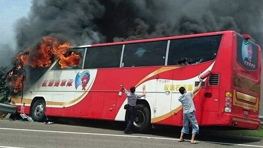 In this photo provided by Yan Cheng, a policeman and another man try to break the windows of a burning tour bus on the side of a highway in Taoyuan, Taiwan, Tuesday, July 19, 2016. The tour bus carrying visitors from China burst into flames on a busy highway near Taiwan's capital on Tuesday, burning to death over 20 people on board, officials said .(Yan Cheng/Scoop Commune via AP)