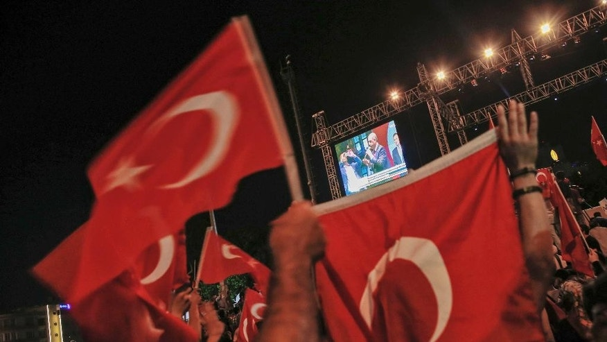 People gathered in Taksim Square in Istanbul to protest against the attempted coup, watch a pre-recorded video message by Turkish President Recep Tayyip Erdogan, early Tuesday, July 19, 2016. The Turkish government accelerated its crackdown on alleged plotters of the failed coup against Erdogan. The rebellion, which saw warplanes firing on key government installations and tanks rolling into major cities, was quashed by loyal government forces and masses of civilians who took to the streets. (AP Photo/Emrah Gurel)
