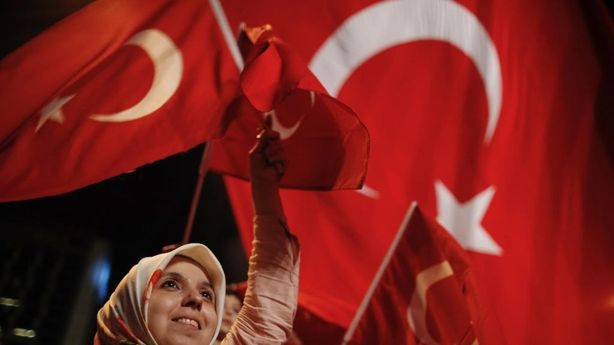 A woman waves Turkish flags during a rally against the attempted coup in Taksim Square in Istanbul, protesting against the attempted coup, Monday, July 18, 2016. The Turkish government accelerated its crackdown on alleged plotters of the failed coup against President Recep Tayyip Erdogan. The rebellion, which saw warplanes firing on key government installations and tanks rolling into major cities, was quashed by loyal government forces and masses of civilians who took to the streets. (AP Photo/Emrah Gurel)
