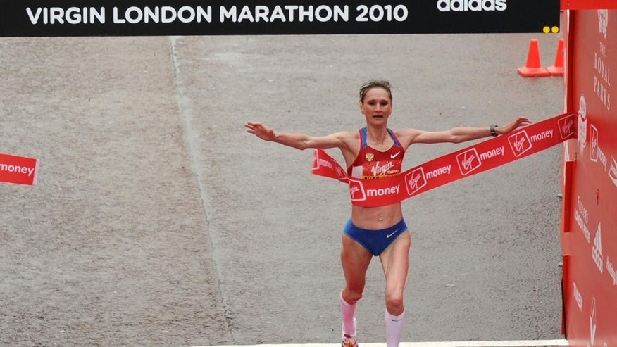 FILE - This is a Sunday April 25, 2010.  file photo of Russia's Liliya Shobukhova as she crosses the finish line to win the London Marathon, in London. London Marathon organizers said Tuesday July 19, 2016 that  a British court has ordered Russian marathon runner Liliya Shobukhova to repay prize and appearance money after being banned for doping.  (AP Photo/Tom Hevezi, File)