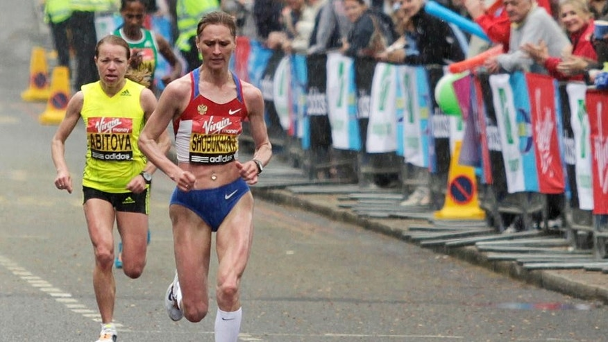 FILE - This is a Sunday April 25, 2010.  file photo of Russia's Liliya Shobukhova as she runs in front of her compatriot Inga Abitova in central London as they competes in the annual London Marathon race. Shobukhova won the women's race and Abitova finished second. London Marathon organizers said Tuesday July 19, 2016 that  a British court has ordered Russian marathon runner Liliya Shobukhova to repay prize and appearance money after being banned for doping. (AP Photo/Lefteris Pitarakis, File)