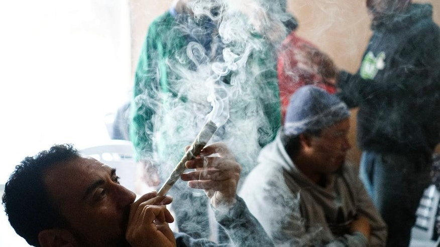 In this July 16, 2016 photo, a competitor smokes a joint during the fifth annual Cannabis Cup, a competition for best marijuana, in Montevideo, Uruguay. At the tournament over the weekend, a panel of regional experts judged entries for aroma, flavor, effects and strength before picking the winners of the best indoor and outdoor crops. (AP Photo/Matilde Campodonico)