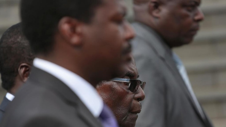 Zimbabwean President Robert Mugabe,centre, is seen during the burial of Charles Utete, the former British Colony First chief secretary to the Cabinet  in Harare, Tuesday, July.19, 2016. Zimbabwe's president on Tuesday attacked the pastor who organized a nationwide strike against the government, saying he should move to another country if he's unhappy with conditions at home. (AP Photo/Tsvangirayi Mukwazhi)