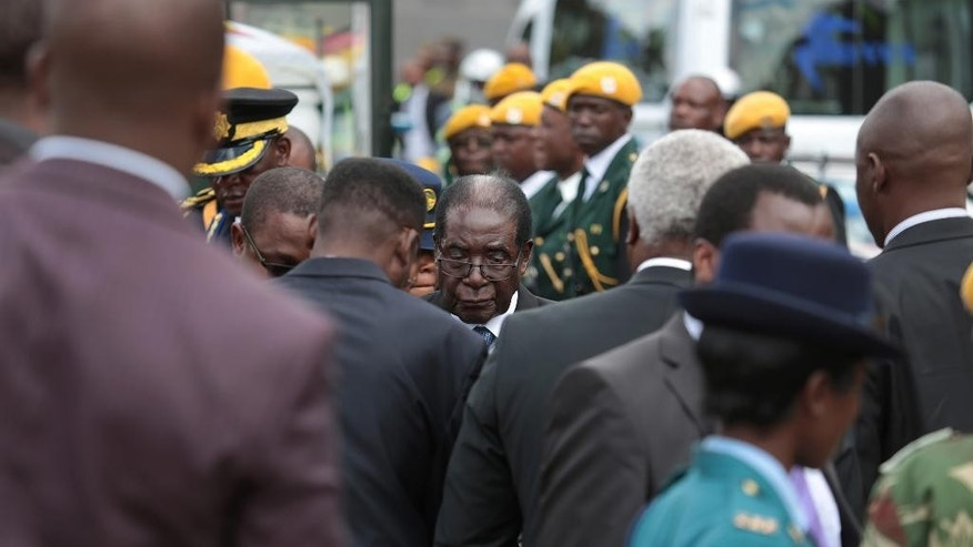 Zimbabwean President Robert Mugabe,centre,is seen during the burial of Charles Utete, the former British Colony First chief secretary to the Cabinet in Harare, Tuesday,  July 19, 2016. Zimbabwe's president on Tuesday attacked the pastor who organized a nationwide strike against the government, saying he should move to another country if he's unhappy with conditions at home. (AP Photo/Tsvangirayi Mukwazhi)