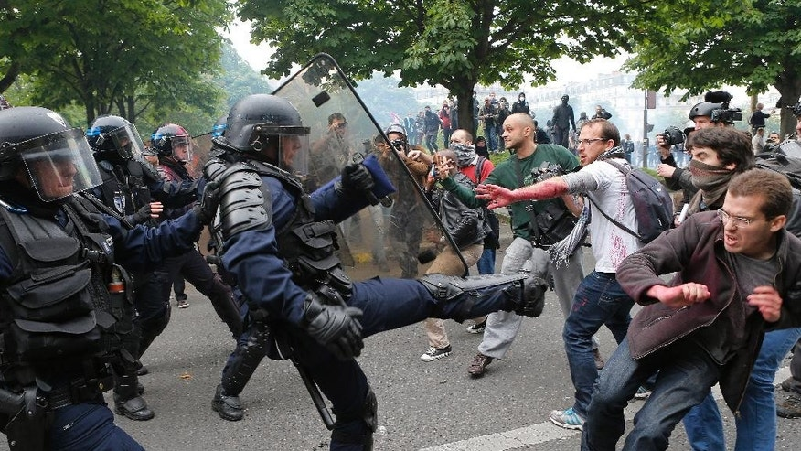 FILE - This Thursday, May 26, 2016 file photo shows riot police officers clashing with protestors during a demonstration held as part of nationwide labor actions in Paris, France. A deeply divisive labor bill has been definitively adopted by the French Parliament after the government used a special measure to force it through without a vote. (AP Photo/Francois Mori, File)