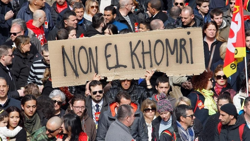 "FILE - This Wednesday, March, 9, 2016 file photo shows workers and students demonstrating against a labor law bill in Marseille, southern France.  Banner reads: ""No El Khomri"", referring to French Labor Minister Myriam El Khomri. A deeply divisive labor bill has been definitively adopted by the French Parliament after the government used a special measure to force it through without a vote. (AP Photo/Claude Paris, File)"