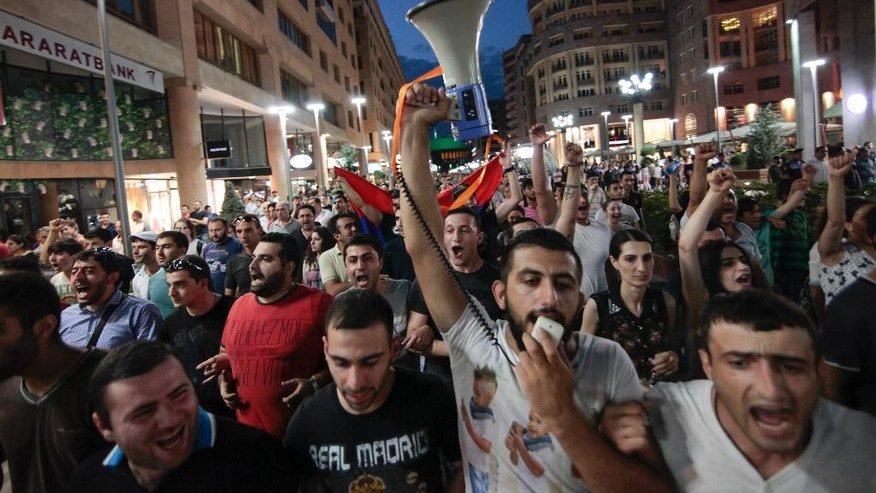 Protesters take a part in a peaceful march in Yerevan, Armenia, Monday, July 18, 2016. About two hundred opposition supporters reached an agreement with police to hold the march as long as they did not march to the besieged police station. (Aram Kirakosyan/PAN Photo via AP)