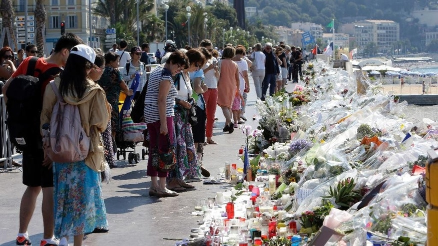 People look at flowers and messages placed along the beach of the Promenade des Anglais in Nice, southern France, Tuesday, July 19, 2016. Joggers, cyclists and sun-seekers are back on Nice's famed Riviera coast, a further sign of normal life returning on the Promenade des Anglais where dozens were killed in last week's Bastille Day truck attack. (AP Photo/Claude Paris)