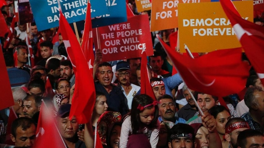 Supporters of Turkish President Recep Tayyip Erdogan hold banners and waves their national flags, during a rally at Kizilay main square, in Ankara, Turkey, Wednesday, July 20, 2016.  U.S. Secretary of State John Kerry is calling on Turkey to provide hard evidence that a U.S.-based cleric was behind a foiled coup attempt last weekend if it wants him extradited.  (AP Photo/Hussein Malla)
