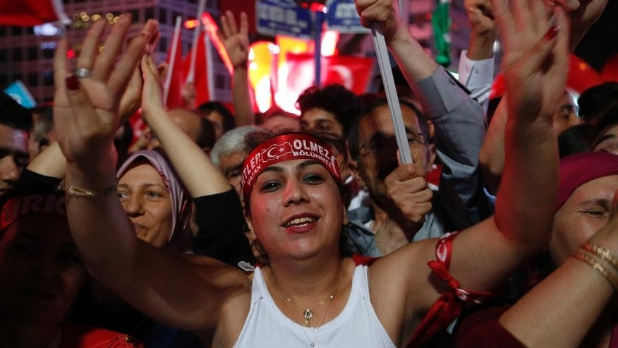 Supporters of Turkish President Recep Tayyip Erdogan shouts slogans during a pro-government rally at Kizilay main square, in Ankara, Turkey, Wednesday, July 20, 2016. Cracking down on alleged subversives in education, Turkey said Wednesday that it will close more than 600 private schools and dormitories following an attempted coup, spurring fears that the state's move against perceived enemies is throwing key institutions in the NATO ally into disarray. (AP Photo/Hussein Malla)