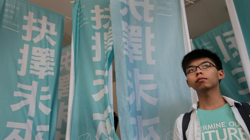 "Teen protest leader Joshua Wong stands outside a magistrate's court in Hong Kong, Thursday, July 21, 2016. A Hong Kong court on Thursday found teen protest leader Wong guilty of taking part in an illegal rally that sparked massive student-led pro-democracy protests two years ago. The banners read ""Determine our future."" (AP Photo/Vincent Yu)"