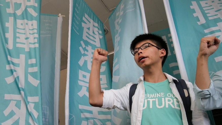 "Teen protest leader Joshua Wong shouts slogans outside a magistrate's court in Hong Kong, Thursday, July 21, 2016. A Hong Kong court on Thursday found teen protest leader Wong guilty of taking part in an illegal rally that sparked massive student-led pro-democracy protests two years ago. The banner reads ""Determine our future."" (AP Photo/Vincent Yu)"