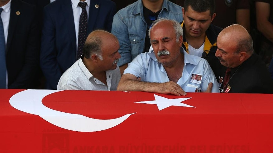 The father of a Turkish policeman mourns over his son's coffin during his funeral procession, in Ankara, Turkey, Wednesday, July 20, 2016. Turkey on Wednesday intensified a sweeping crackdown on the media, the military, the courts and the education system following an attempted coup, targeting tens of thousands of teachers and other state employees for dismissal in a purge that raised concerns about basic freedoms and the effectiveness of key institutions. (AP Photo/Hussein Malla)