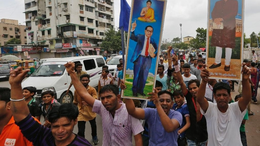 Members of India's low-caste Dalit community carry portraits of their leader Bhim Rao Ambedkar and shout slogans in Ahmadabad, India, Wednesday, July 20, 2016. They were protesting after four men belonging to the Dalit community were beaten while trying to skin a dead cow in western India. (AP Photo/Ajit Solanki)