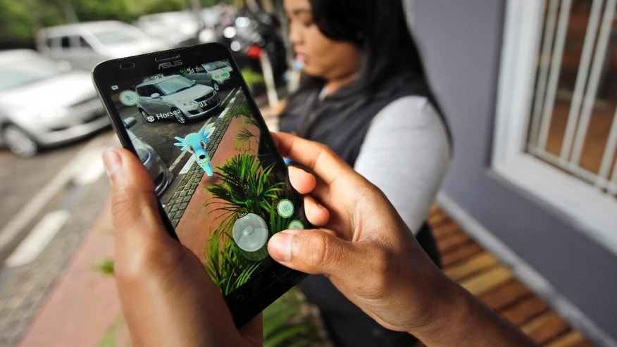 "In this Monday, July 18, 2016 photo, people play ""Pokemon Go"" in Jakarta, Indonesia. Indonesian authorities banned the playing of ""Pokemon Go"" from the presidential palace on Wednesday, July 20, 2019, as they voiced worries that the game could be a security risk. (AP Photo/Achmad Ibrahim)"