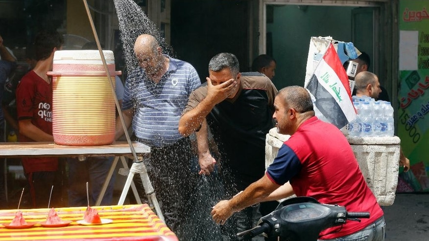 People cool off from the summer heat by using an open air shower in Baghdad, Iraq, Wednesday, July, 20, 2016. Iraqis are enduring the year's hottest day to date, with temperatures soaring to 51 Celsius degrees (123.8 Fahrenheit) in Baghdad and as much as 53 Celsius (127.4 Fahrenheit) in the southern part of the country. (AP Photo/Karim Kadim)