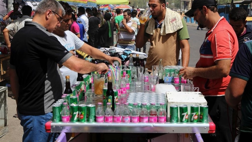 People cool off the summer heat by drinking iced juice in Baghdad, Iraq, Wednesday, July, 20, 2016. Iraqis are enduring the year's hottest day to date, with temperatures soaring to 51 Celsius degrees (123.8 Fahrenheit) in Baghdad and as much as 53 Celsius (127.4 Fahrenheit) in the southern part of the country. (AP Photo/Karim Kadim)