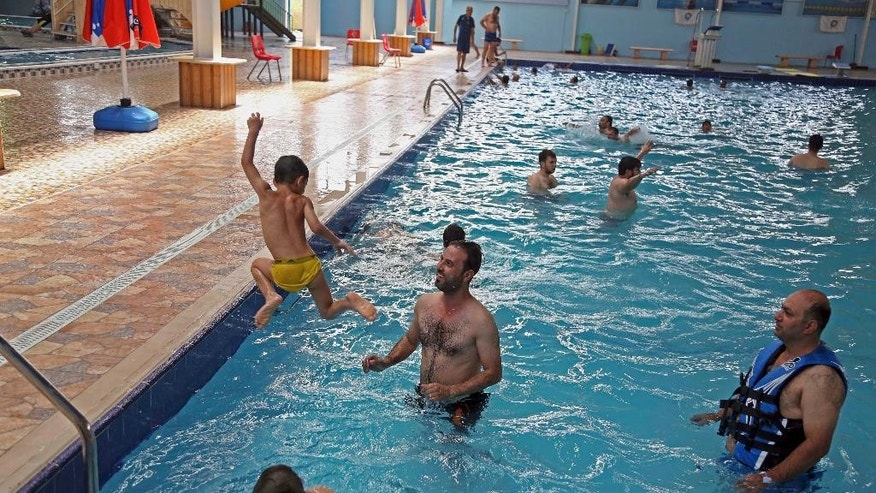 People escape the searing summer heat swimming pool in Baghdad, Iraq, Wednesday, July, 20, 2016. Iraqis are enduring the year's hottest day to date, with temperatures soaring to 51 Celsius degrees (123.8 Fahrenheit) in Baghdad and as much as 53 Celsius (127.4 Fahrenheit) in the southern part of the country. (AP Photo/Karim Kadim)