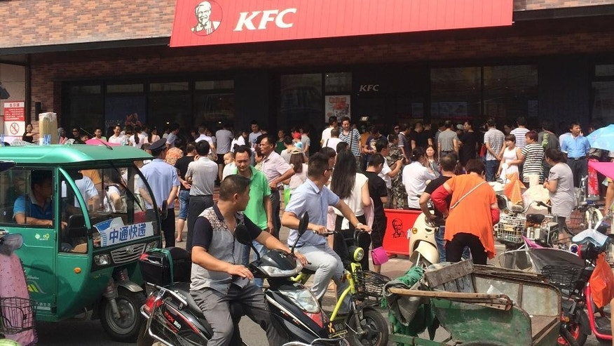 In this photo taken on Tuesday, July 19, 2016 and released by Guo Lu, motorists watch people gather to protest outside a KFC restaurant outlet in Baoying county in east China's Jiangsu province. In an apparent attempt to head off large-scale street demonstrations, Chinese state newspapers have criticized scattered protests against KFC restaurants and other U.S. targets sparked by an international tribunal's ruling that denied Beijing's claim to virtually the entire South China Sea. (Guo Lu via AP)