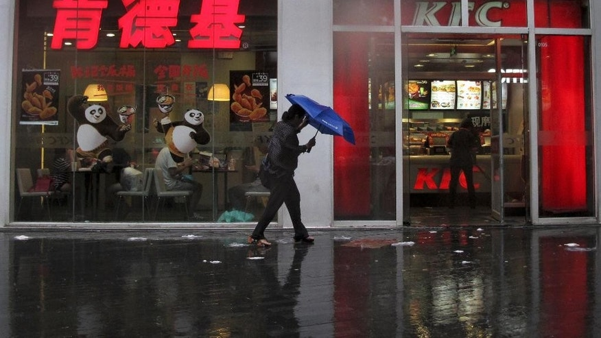 A woman holds an umbrella shield from the rain as she walks past a KFC restaurant outlet in Beijing, Wednesday, July 20, 2016. In an apparent attempt to head-off large-scale street demonstrations, Chinese state newspapers have criticized scattered protests against KFC restaurants and other U.S. targets sparked by an international tribunal's ruling last week that denied Beijing's claim to virtually the entire South China Sea. (AP Photo/Andy Wong)