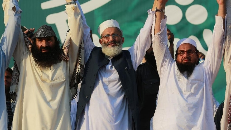 "Pakistani religious leaders, from right Hafiz Saeed, chief of Jamaat-ud-Dawa joins hands with Sirajul Haq, center, and the leader of Hizbul Mujahideen Syed Salahuddin, left, during an anti-Indian rally in Islamabad, Pakistan, Wednesday, July 20, 2016. Pakistan Prime Minister Nawaz Sharif vowed that his country would continue extending political moral and diplomatic support to Kashmiris. He urged his countrymen to observe ""black day"" to express solidarity with ""Kashmiris who are facing atrocities at the hands of Indian forces."" (AP Photo/B.K. Bangash)"