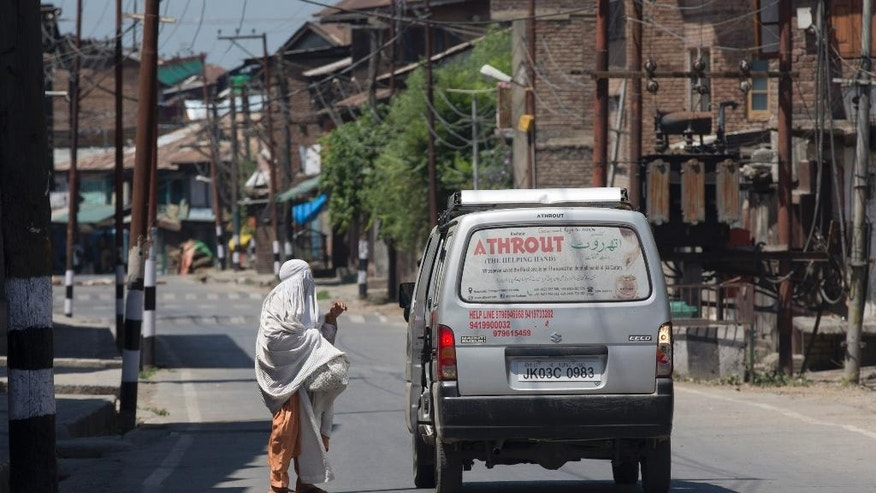 A burqa clad Kashmiri woman asks for lift during the 12th straight day of curfew in Srinagar, Indian controlled Kashmir, Wednesday, July 20, 2016. The region's largest street protests in recent years erupted last week after Indian troops killed Burhan Wani, the popular young leader of the largest rebel group fighting against Indian rule in Kashmir.(AP Photo/Dar Yasin)