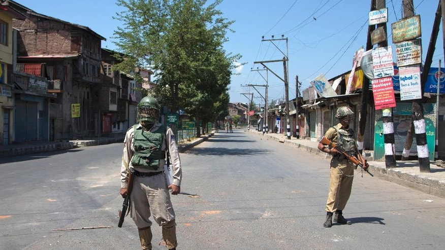 Indian paramilitary soldiers stand guard during the 12th straight day of curfew in Srinagar, Indian controlled Kashmir, Wednesday, July 20, 2016. The region's largest street protests in recent years erupted last week after Indian troops killed Burhan Wani, the popular young leader of the largest rebel group fighting against Indian rule in Kashmir.(AP Photo/Dar Yasin)