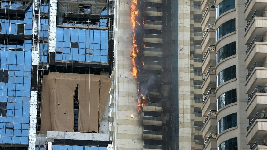 A fire rages at a skyscraper in the Dubai Marina section of Dubai, United Arab Emirates, Wednesday, July 20, 2016. The residential skyscraper in Dubai caught fire in the densely populated Marina district, sending columns of smoke into the air and pieces of the building's facade tumbling below. It's the latest in a number of skyscraper fires across the United Arab Emirates in recent months. The most prominent was a New Year's inferno at a 63-story residence near the world's tallest tower. (AP Photo/Adam Schreck)