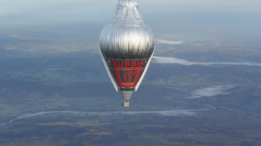 In this Tuesday, July 12, 2016 photo released Wednesday, July 20, 2016 by Morton, Russian adventurer Fedor Konyukhov floats at more than 6,000 meters (20,000 feet) above an area close to Northam in Western Australia state in his helium and hot-air balloon as he makes a record attempt to fly solo in a balloon around the world nonstop. Konyukhov, 65, was battling sleep deprivation, freezing temperatures and ice in his oxygen mask as he nears the end of his record attempt to fly solo around the world nonstop, his son said on Wednesday July 20, 2016. (Oscar Konyukhov/Morton via AP)
