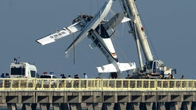 A damaged seaplane is lifted from the pier in Shanghai Wednesday, July 20, 2016. The seaplane making its inaugural flight crashed into a highway bridge on Wednesday, killing several people on board, state media reported. (Chinatopix via AP)