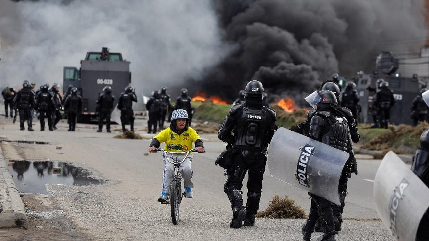 A man rides his bicycle past police clashing with striking truckers in Bogota, Colombia, Wednesday, July 20, 2016. Hundreds of truckers clashed with police on Wednesday on the 41st day of their strike which has made food scarce in some areas of the country. Truckers are demanding a higher price for freight, lower fuel prices and fewer license regulations for cargo. (AP Photo/Fernando Vergara)