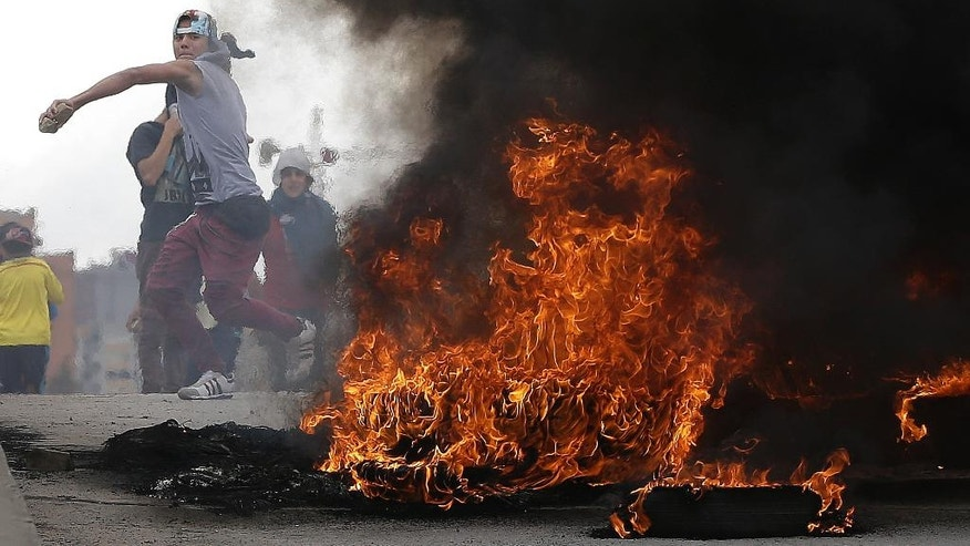 A man throws stones at police during a truckers strike in Bogota, Colombia, Wednesday, July 20, 2016. Hundreds of truckers clashed with police on Wednesday on the 41st day of their strike which has made food scarce in some areas of the country. Truckers are demanding a higher price for freight, lower fuel prices and fewer license regulations for cargo. (AP Photo/Fernando Vergara)