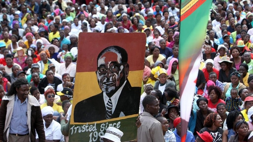Thousands of Mugabe supporters supporters carry his portrait while gathering at the party headquarters in Harare, Wednesday, July, 20, 2016. Tens of thousands of supporters of Zimbabwe's ruling party are marching in the capital in response to a series of recent protests against the government of 92-year-old President Robert Mugabe. The supporters sang and chanted slogans Wednesday in support of Mugabe, who has been in power for 36 years. (AP Photo/Tsvangirayi Mukwazhi)