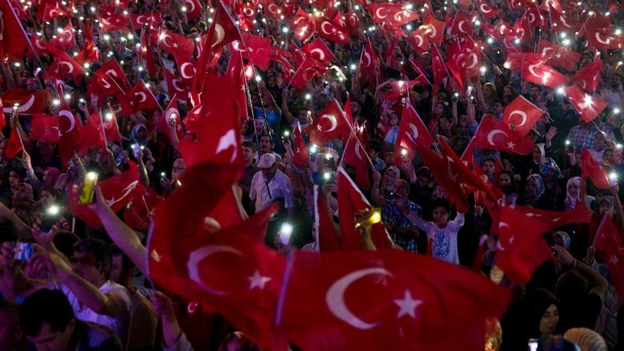 Government supporters wave Turkish flags during a rally in Taksim Square, Istanbul, Tuesday, July 19, 2016. The Turkish government accelerated its crackdown on alleged plotters of the failed coup against President Recep Tayyip Erdogan. The rebellion, which saw warplanes firing on key government installations and tanks rolling into major cities, was quashed by loyal government forces and masses of civilians who took to the streets.(AP Photo/Petros Giannakouris)