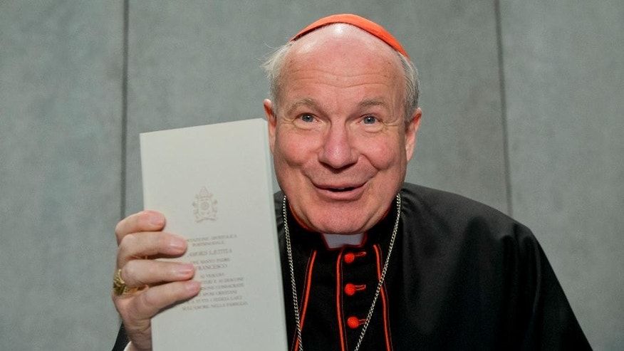 FILE -  This Friday, April 8, 2016 file photo shows Cardinal Christoph Schoenborn holding a copy of the post-synodal apostolic exhortation ' Amoris Laetitia ' (The Joy of Love) during a press conference at the Vatican. The Vatican is striking back at conservative critics of Pope Francis' landmark document on family life, ratcheting up its defense of the pope with new vigor as bishops begin implementing the document in dioceses around the world.  (AP Photo/Andrew Medichini)