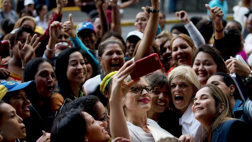 Opposition Congresswoman Adriana Delia, center, poses for a photo with supporters during a protest asking for a referendum against Venezuela's President Nicolas Maduro, outside the National Electoral Council, in Caracas, Venezuela, Tuesday, July 19, 2016. The opposition is pushing for a recall referendum to cut short Maduro's term. They accuse elections officials of dragging their feet to delay the process. (AP Photo/Fernando Llano)