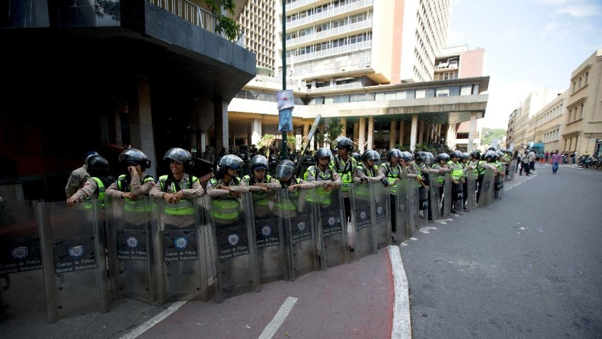 Bolivarian National Police officers form a cordon outside the National Electoral Council, as opposition members hold a protest asking for a referendum against Venezuela's President Nicolas Maduro, in Caracas, Venezuela, Tuesday, July 19, 2016. The opposition is pushing for a recall referendum to cut short Maduro's term. They accuse elections officials of dragging their feet to delay the process. (AP Photo/Fernando Llano)