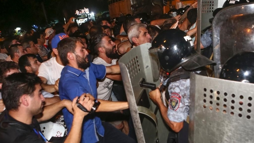 Armenian protesters clash with police officers near the area around a police station in Yerevan, Armenia, Wednesday, July 20, 2016.  Demonstrators and police have clashed outside a police station in the Armenian capital where armed supporters of a jailed opposition leader have held hostages for four days. (Hrant Khachatryan/PAN Photo via AP)
