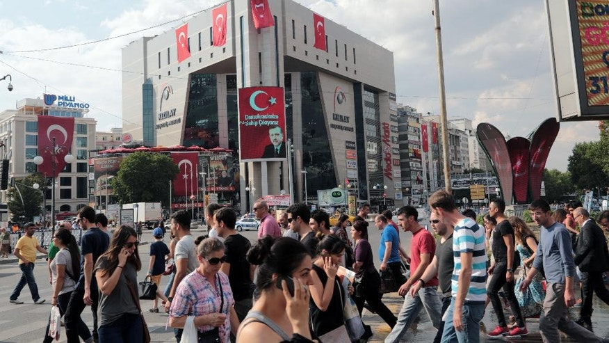 People walk in Kizilay Square with a poster of Turkey's President Recep Tayyip Erdogan in the background in Ankara, Turkey, Thursday, July 21, 2016. Turkish lawmakers declared a three-month state of emergency Thursday, overwhelmingly approving President Recep Tayyip Erdogan's request for sweeping new powers to expand a crackdown in the aftermath of last week's coup. Parliament voted 346-115 to approve the national state of emergency, which will give Erdogan the authority to extend detention times for suspects and issue decrees that have the force of law without parliamentary approval, among other powers.(AP Photo/Burhan Ozbilici)