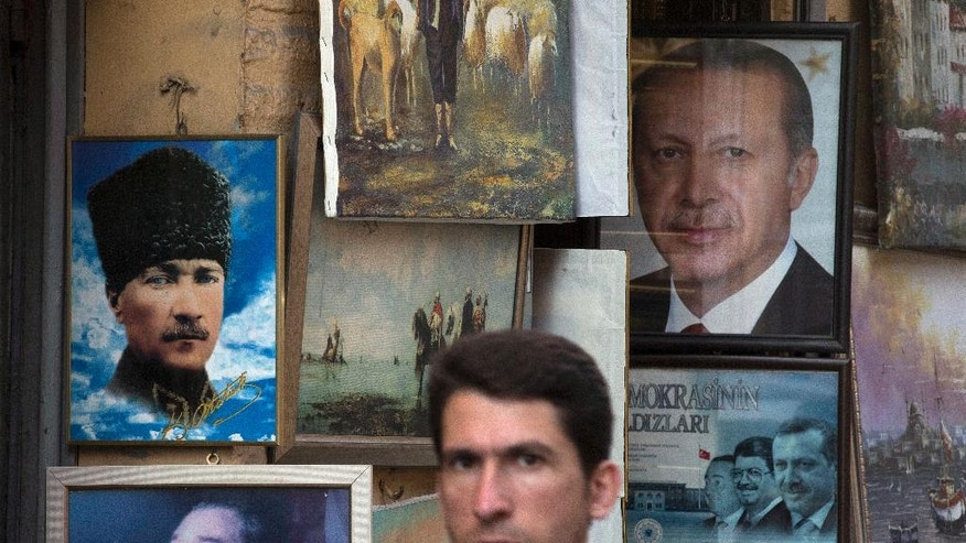 "The portraits of Turkey's founder Kemal Ataturk, left and President Recep Tayyip Erdogan, right, are seen in a shop window in central Istanbul, Thursday, July 21, 2016. President Erdogan on Wednesday declared a three-month state of emergency following a botched coup attempt, declaring he would rid the military of the ""virus"" of subversion and giving the government sweeping powers to expand a crackdown that has already included mass arrests and the closure of hundreds of schools. (AP Photo/Petros Giannakouris)"