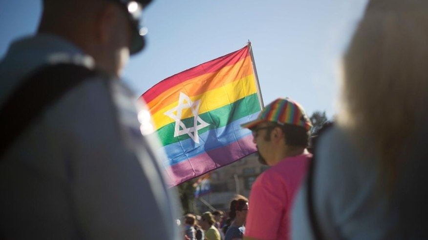 Israeli police officers watch as people take part in the annual gay pride parade in central Jerusalem, Thursday, July 21, 2016. Thousands of people waving rainbow flags marched through downtown Jerusalem Thursday in the city's annual gay pride parade in a defiant show of force a year after an extremist ultra-Orthodox Jew stabbed a 16-year-old girl to death at the march. (AP Photo/Ariel Schalit)