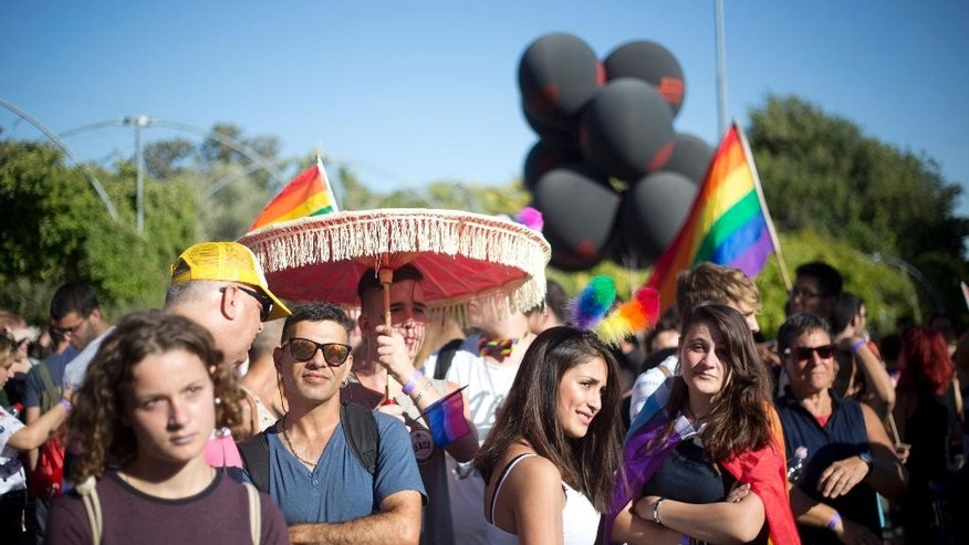 People take part in the annual gay pride parade in central Jerusalem, Thursday, July 21, 2016. Thousands of people waving rainbow flags marched through downtown Jerusalem Thursday in the city's annual gay pride parade in a defiant show of force a year after an extremist ultra-Orthodox Jew stabbed a 16-year-old girl to death at the march. (AP Photo/Ariel Schalit)
