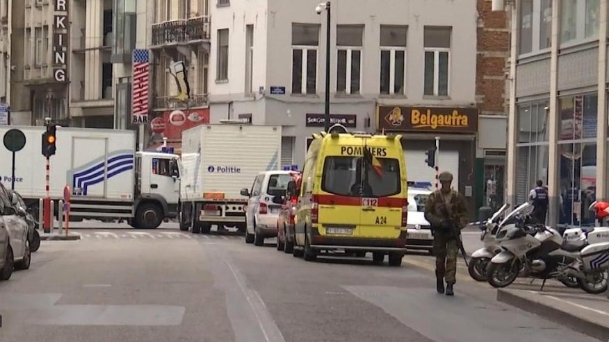 In this framegrab taken from APTN, a soldier walks along a street in Brussels, Belgium, Wednesday July 20, 2016. Police in Brussels say they arrested a man acting suspiciously and wearing heavy clothes with wires hanging out, in the area of place Monnaie. Police closed the area and evacuated people surrounding the area. (AP Photo/APTN)