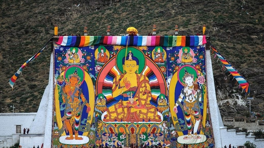 In this Wednesday, July 20, 2016 photo released by Xinhua News Agency, a huge Thangka Buddha portrait is unveiled at the Zhaxi Lhunbo Lamasery during a Buddhist ritual event in Xigaze in southwest China's Tibet Autonomous Region. China's hand-picked Panchen Lama is presiding over a key Buddhist ritual being held in Tibet for only the first time in 50 years, in a move criticized by overseas Tibetan groups. (Purbu Zhaxi/Xinhua via AP)
