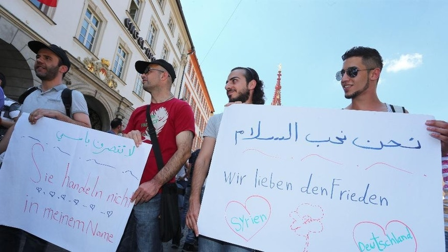 Refugees, some of whom come from Syria, and their supporters demonstrate with posters written with 'we love peace' , right, and 'they aren't acting in my name' in downtown Wuerzburg, Germany, Wednesday July 20, 2016. They are responding to the attack by a suspected Afghan refugee who attacked and critically injured passengers with an axe and knife in a regional train near Wuerzburg, (Karl-Josef Hildenbrand/dpa via AP)