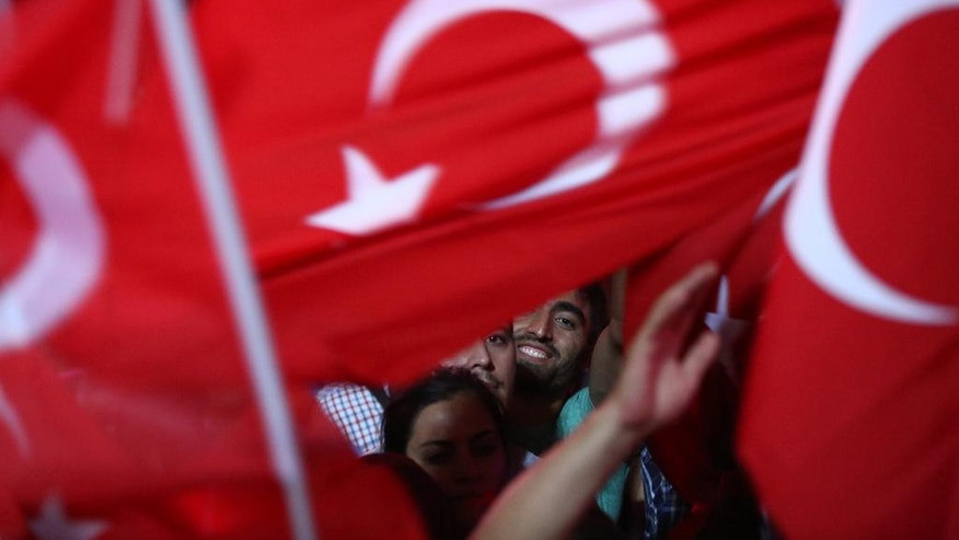 Supporters of Turkish President Recep Tayyip Erdogan wave their national flags during a pro-government rally at Kizilay main square, in Ankara, Turkey, Wednesday, July 20, 2016.  U.S. Secretary of State John Kerry is calling on Turkey to provide hard evidence that a U.S.-based cleric was behind a foiled coup attempt last weekend if it wants him extradited. (AP Photo/Hussein Malla)